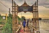 Seorang pengunjung sedang melintas di gerbang masuk kawasan ekowisata mangrove pantai Mekar di Kecamatan Muaragembong, Kabupaten Bekasi, Jawa Barat. (Antaranews Megapolitan/Foto: Pradita Kurniawan Syah).