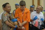 Kapolresta Denpasar, Kombes Pol Ruddi Setiawan (kiri) memperlihatkan orangutan yang hendak diselundupkan oleh warga negara Rusia Zhestkov Andrei (tengah), dalam konferensi pers di Gedung Wisti Sabha Angkasa Pura, Badung, Bali, Senin (25/3/2019). Warga negara Rusia tersebut ditangkap pada Jumat (22/3) di Bandara Ngurah Rai karena berupaya menyelundupkan orangutan untuk dijual di negaranya sehingga terancaman hukuman lima tahun penjara dengan denda mencapai Rp100 juta. (ANTARA FOTO)