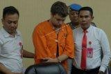 Polisi menggiring warga negara Rusia Zhestkov Andrei (tengah) yang menjadi tersangka kasus penyelundupan orangutan dalam konferensi pers di Gedung Wisti Sabha Angkasa Pura, Badung, Bali, Senin (25/3/2019). Warga negara Rusia tersebut ditangkap pada Jumat (22/3) di Bandara Ngurah Rai karena berupaya menyelundupkan orangutan untuk dijual di negaranya sehingga terancaman hukuman lima tahun penjara dengan denda mencapai Rp100 juta. (ANTARA FOTO)