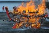 Umat Buddha mendokumentasikan acara ritual bakar replika kapal di Vihara Avalokitesvara, Pamekasan, Jawa Timur, Minggu (24/3/2019). Ritual bakar kapal tersebut dimaksudkan sebagai persembahan kepada dewa guna memperoleh kesuksesan dan keselamatan dalam menggapai masa depan. (ANTARA FOTO)