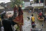 Dalang membawakan kesenian wayang golek di area banjir pada acara Pentas Bandung Lautan Banjir di Bojongasih, Dayeuhkolot, Kabupaten Bandung, Jawa Barat, Minggu (14//4/2019). Kegiatan tersebut merupakan bentuk protes dari warga serta menjadi kegiatan untuk menghibur warga yang telah terdampak banjir sejak hampir sebulan lalu akibat luapan sungai Citarum. ANTARA JABAR/Novrian Arbi/agr.