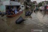 Warga menggunakan perahu untuk melihat sejumlah kesenian yang ditampilkan di area banjir pada acara Pentas Bandung Lautan Banjir di Bojongasih, Dayeuhkolot, Kabupaten Bandung, Jawa Barat, Minggu (14//4/2019). Kegiatan tersebut merupakan bentuk protes dari warga serta menjadi kegiatan untuk menghibur warga yang telah terdampak banjir sejak hampir sebulan lalu akibat luapan sungai Citarum. ANTARA JABAR/Novrian Arbi/agr.