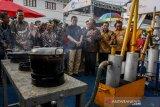 Menteri ESDM Ignasius Jonan (tengah) mendengarkan arahan saat melihat mesin produksi gas hemat energi yang dipamerkan pada acara peringatan ke-49 Hari Bumi Internasional di Museum Geologi Bandung, Jawa Barat, Sabtu (27/4/2019). Kegiatan yang bertema Harmoni Indonesia melalui Green Energy tersebut sebagai bentuk peranan Kementerian ESDM dalam sosialiasasi dan mengajak masyarakat untuk menumbuhkan kesadaran dalam menjaga dan melestarikan bumi. ANTARA JABAR/Novrian Arbi/agr