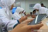 Sejumlah siswa memperlihatkan soal ujian melalui smartphone saat mengikuti simulasi ujian kenaikan kelas berbasis android di Madrasah Tsanawiyah Negeri (MTsN) 3 Meulaboh, Aceh Barat, Selasa (30/4/2019). Simulasi tersebut bertujuan untuk menguji kemampuan dan kesiapan siswa serta untuk memastikan dan mengukur bisa tidaknya melaksanakan ujian kenaikan kelas berbasis smartphone. (Antara Aceh/Syifa Yulinnas)