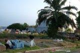 Wahab dan istrinya Fitri membersihkan makam anggota keluarga mereka saat melakukan ziarah kubur di Tempat Pemakaman Umum (TPU) Muslim yang berdekatan dengan TPU Kristen juga di samping gereja, di Desa Purwodadi, Sunggal, Deli Serdang, Sumatera Utara, Jumat (3/5/2019). Ziarah kubur merupakan salah satu tradisi yang dilakukan umat Islam menjelang bulan Ramadhan. (Antara Sumut/Irsan)