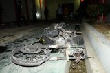 Warga melihat bangkai mobil yang rusak dampak kerusuhan di Lapas Narkotika Kelas III Langkat, di Langkat, Sumatera Utara, Kamis (16/5/2019). Akibat peristiwa kerusuhan yang dilakukan para narapidana di Lapas tersebut mengakibatkan tiga mobil dan dua sepeda motor petugas rusak terbakar dan ratusan napi melarikan diri. ANTARA FOTO