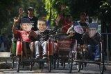 Warga menaiki becak sambil menggunakan penutup wajah bergambar pasangan capres cawapres peserta Pemilu 2019, Joko Widodo- Ma'ruf Amin dan Prabowo Subianto -Sandiaga Uno saat aksi damai di Solo, Jawa Tengah, Jumat (24/5/2019). Dalam aksi tersebut mereka berharap capres nomor urut 01 Joko Widodo dan capres nomor urut 02 Prabowo Subianto segera bertemu guna rekonsiliasi pascapilpres 2019. ANTARA FOTO