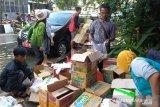 Relawan GMSS SKM Samarinda sedang mengeluarkan bantuan dari dus untuk dikemas per paket