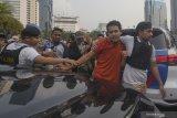 Petugas amakan seorang pria saat aksi di MK