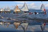 Nelayan beradu cepat memacu perahunya pada kompetisi perahu layar di Pantai Waru doyong, Banyuwangi, Jawa Timur, Minggu (16/6/2019). Kompetisi yang diikuti 95 nelayan dari Pulau Jawa, Madura dan Bali itu untuk memperingati hari Bhayangkara ke-73 itu, ajang silaturahmi antarnelayan dan untuk mengembangkan sektor pariwisata. ANTARA FOTO/Budi Candra Setya/nym.