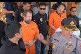 Polisi menggiring dua warga negara Rusia Robert Haupt (kedua kanan) dan Georgii Zhukov (kedua kiri) yang terlibat kasus perampokan money changer saat pelimpahan kasus tersebut untuk proses persidangan, di Mapolresta Denpasar, Bali, Senin (17/6/2019). Kasus perampokan money changer di Benoa, Kuta Selatan pada bulan Maret 2019 itu melibatkan empat warga negara Rusia yaitu dua orang menjalani proses hukum, seorang tewas tertembak dan seorang lagi masih buron. ANTARA FOTO/Nyoman Hendra Wibowo/nym