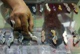 Perajin menata kujang berbahan batu akik di Workshop Saung Batu Ki Nata, Sukaharja, Karawang, Jawa Barat, Selasa (18/6/2019). Perajin di workshop tersebut mampu memproduksi 50 - 100 kujang per bulan dengan harga jual Rp150 ribu - Rp1,5 juta per kujangnya tergantung dari bahan dan ukurannya dan sudah dipasarkan ke sejumlah negara seperti Arizona, Argentina, London, Malaysia, Singapura. ANTARA JABAR/M Ibnu Chazar/agr
