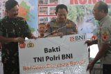 Panglima TNI Marsekal TNI Hadi Tjahjanto (Kiri) dan Kapolri Jenderal Pol Tito Karnavian (tengah) menyerahkan bantuan dana Bakti TNI, Polri dan BNI secara simbolis kepada Bupati Konawe Utara Ruksamin (kanan) di Rujab Bupati Konawe Utara, Sulawesi Tenggara, Sabtu (22/6/2019). Bantuan tersebut diberikan untuk rehabilitasi pascabanjir bagi para korban di Kabupaten Konawe Utara. ANTARA FOTO/Jojon/wsj.