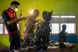 Siswa menyelesaikan pembuatan robot polisi berbahan onderdil motor bekas di SMK Karya Utama, Warung Bambu, Karawang, Jawa Barat, Senin (24/6/2019). Robot tersebut menggambarkan polisi menggendong anak kecil yang diciptakan oleh siswa jurusan teknik perawatan mekanik industri untuk hadiah pada HUT ke - 73 Bhayangkara. ANTARA FOTO/M Ibnu Chazar/nym.