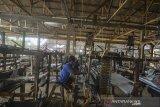 Pekerja menyelesaikan pembuatan tenun sutra menggunakan alat tradisional di rumah produksi Sabilulungan Desa Cipondok, Kabupaten Tasikmalaya, Jawa Barat, Senin (24/6/2019). Menurut perajin permintaan pasar kain sutra masih belum terpenuhi, karena perajin hanya mampu memproduksi 150 potong kain sutra per bulan akibat kesulitan bahan baku benang sutra, dan pekerja, padahal permintaan pasar untuk Jateng, Jabar dan Jakarta mencapai 500 potong, dengan harga Rp500 ribu - Rp2,5 juta per potong. ANTARA JABAR/Adeng Bustomi/agr