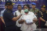 Kepala Bea Cukai Kantor Wilayah (Kanwil) Jawa Barat Saifullah Nasution (kiri) menutup wajah tersangka penyeludupan narkotika dengan masker saat pengungkapan kasus narkotika di Bea Cukai Kanwil Jawa Barat, Bandung, Rabu (26/6/2019). Petugas Bea Cukai Kanwil Jawa Barat beserta tim interdiksi terpadu Bandara Husein Sastranegara berhasil menangkap tersangka asal Afrika yang membawa 1.595 methamphetamine senilai Rp 3,1 miliar yang diseludupkan di pakaian dalamnya saat mendarat di Bandara Husein Sastranegara. ANTARA JABAR/Raisan Al Farisi/agr
