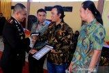 Kapolres Aceh Barat AKBP Raden Bobby Aria Prakasa (kiri) menyerahkan piagam penghargaan kepada lembaga penggiat lingkungan yang terdiri dari Forum Konservasi Leuser (FKL), WildLife Conservation Society (WCS) dan Yayasan Hutan, Alam dan Lingkungan Aceh (HAkA) saat syukuran HUT ke-73 Bhayakara di Mapolsek Meureubo, Aceh Barat, Aceh, Rabu (10/7/2019). Penyerahan penghargaan tersebut sebagai bentuk terima kasih dengan pihak terkait yang telah membantu dan mendukung tugas kepolisian dalam memberantas tindak kejahatan lingkungan. (Antara Aceh/Syifa Yulinna)
