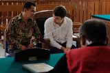 Warga negara Rusia, Andrei Zhestkov (kedua kanan) mendapat penjelasan dari petugas penerjemah saat menjalani sidang kasus penyelundupan orangutan di Pengadilan Negeri Denpasar, Bali, Kamis (11/7/2019). Majelis hakim menjatuhkan setahun penjara dan denda Rp10 juta subsider 2 bulan pidana kurungan bagi Andrei Zhestkov karena dinyatakan terbukti bersalah yaitu berupaya menyelundupkan orangutan lewat Bandara Ngurah Rai ke negaranya pada 22 Maret 2019. ANTARA FOTO/Nyoman Hendra Wibowo/nym.
