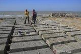 Pekerja menyelesaikan pembuatan beton pemecah ombak di pantai Juntinyuat, Indramayu, Jawa Barat, Minggu (14/7/2019). Beton pemecah ombak yang dipasang di beberapa titik di pantai tersebut untuk menahan abrasi pantai, serta banjir rob akibat air pasang yang kian mengikis daratan. ANTARA JABAR/Dedhez Anggara/agr