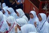 Para peserta didik baru SMP Negeri  2 Depok ketika mendengarkan pengarahan dari Kepala Sekolah Purnomo D Ismawan dalam Masa Pengenalan Lingkungan Sekolah (MPLS).
