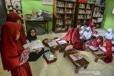 Siswa kelas 2 Sekolah Dasar Negeri (SDN) Cikadongdong mengikuti Kegiatan Belajar Mengajar (KBM) dilantai ruang perpustakaan di Singaparna, Kabupaten Tasikmalaya, Jawa Barat, Rabu (17/7/2018). Akibat kekurangan ruang kelas, sebanyak 19 siswa terpaksa belajar tidak menggunakan kursi, padahal pihak sekolah sudah kerap kali mengajukan kepada pemerintah setempat untuk menyediakan ruang kelas baru namun hingga saat ini belum terealisasi. ANTARA JABAR/Adeng Bustomi/agr
