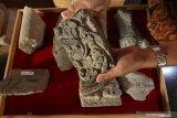 Arkeolog Dinas Kebudayaan dan Pariwisata memperlihatkan potongan batu berukir khas peninggalan kerajaan Kediri yang baru saja ditemukan di museum Bhagawanta Bari, Kediri, Jawa Timur, Rabu (17/7/2019). Arca dan sejumlah potongan batu berukir khas peninggalan kerajaan Kediri tersebut merupakan hasil ekskavasi tim Pusat Penelitian Arkeologi Nasional (Puslit Arkenas) di candi belum jadi (unfinished) situs Adan-adan Kediri. Antara Jatim/Prasetia Fauzani/zk.