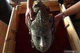 Arkeolog Dinas Kebudayaan dan Pariwisata memasukan potongan kepala arca bodhisatwa yang baru saja ditemukan ke dalam kotak kaca di museum Bhagawanta Bari, Kediri, Jawa Timur, Rabu (17/7/2019). Arca dan sejumlah potongan batu berukir khas peninggalan kerajaan Kediri tersebut merupakan hasil ekskavasi tim Pusat Penelitian Arkeologi Nasional (Puslit Arkenas) di candi belum jadi (unfinished) situs Adan-adan Kediri. Antara Jatim/Prasetia Fauzani/zk.