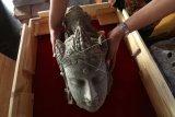 Arkeolog Dinas Kebudayaan dan Pariwisata memasukkan potongan kepala arca Bodhisatwa yang baru saja ditemukan ke dalam kotak kaca di Museum Bhagawanta Bari, Kediri, Jawa Timur, Rabu (17/7/2019). Arca dan sejumlah potongan batu berukir khas peninggalan Kerajaan Kediri tersebut merupakan hasil ekskavasi tim Pusat Penelitian Arkeologi Nasional (Puslit Arkenas) di candi belum jadi (unfinished) situs Adan-Adan Kediri. ANTARA FOTO/Prasetia Fauzani/nym.