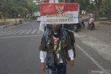 Seorang aktivis demokrasi, Medi Bastoni melakukan aksi jalan mundur di jalan raya Tulungagung, Jawa Timur, Kamis (18/7/2019). Solo aksi yang dimulai dari Pendopo Kabupaten Tulungagung menuju Istana Negara, Jakarta itu dilakukan dalam rangka memperingati HUT ke-74 Kemerdekaan RI sekaligus bentuk dukungan atas terpilihnya kembali Presiden Joko Widodo untuk periode pemerintahan 2019-2024. Antara Jatim/Destyan Sujarwoko/zk