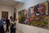 Pengunjung mengamati lukisan yang dipamerkan di sebuah galeri lukis di Kota Madiun, Jawa Timur, Sabtu (20/7/2019) malam. Pameran yang menampilkan puluhan karya 11 perupa dari komunitas Barbaradoz Yogyakarta bertema Patah Tumbuh Liar 2 tersebut rencananya berlangsung hingga 17 Agustus mendatang. Antara Jatim/Siswowidodo/zk.