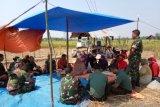 Puluhan prajurit TNI turun ke sawah panen perdana bareng warga