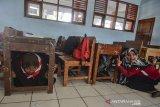 Siswa SMP Negeri 1 Pangandaran menyelamatkan diri dibawah meja saat terjadi gempa bumi pada Simulasi Ekpedisi Desa Tangguh Bencana (Destana) Tsunami didalam kelas sekolah, Desa Pananjung, Kabupaten Pangadaran, Jawa Barat, Sabtu (3/8/2019). Ekspedisi Destana Tsunami pesisir jawa bagian selatan yang diselenggarakan Badan Nasional Penanggulangan Bencana (BNPB) diadakan 24 kabupaten/kota dan 5 provinsiuntuk penguatan kelembagaan daerah serta penguatan ketangguhan aparat didaerah rawan gempa bumi dan tsunami. ANTARA FOTO/Adeng Bustomi/agr