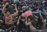 Siswa SMP Negeri 1 Pangandaran menyelamatkan diri berkumpul dititik evakuasi saat terjadi gempa bumi pada Simulasi Ekpedisi Desa Tangguh Bencana (Destana) Tsunami didalam kelas sekolah, Desa Pananjung, Kabupaten Pangadaran, Jawa Barat, Sabtu (3/8/2019). Ekspedisi Destana Tsunami pesisir jawa bagian selatan yang diselenggarakan Badan Nasional Penanggulangan Bencana (BNPB) diadakan 24 kabupaten/kota dan 5 provinsiuntuk penguatan kelembagaan daerah serta penguatan ketangguhan aparat didaerah rawan gempa bumi dan tsunami. ANTARA FOTO/Adeng Bustomi/agr