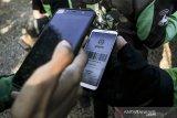 Seorang Mitra Driver (supir) Gojek  memindai kode batang  untuk mendapatkan atribut baru pada acara Festival Apresiasi Mitra Gojek di Armor Kopi, Bandung, Jawa Barat, Sabtu (3/8/2019). Sedikitnya 2000 Mitra Driver Gojek memeriahkan acara yang bertujuan untuk apresiasi sekaligus mengenalkan logo dan membagikan jaket baru sebagai upaya meningkatkan semangat, inovasi dan pelayanan kepada konsumen di Indonesia. ANTARA FOTO/Novrian Arbi/agr