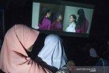 Relawan pembisik menceritakan visual adegan kepada anak tunanetra saat menonton film Keluarga Cemara pada kegiatan Bioskop Harewos di Nuart Sculpture Park, Bandung, Jawa Barat, Minggu (4/8/2019). Kegiatan tersebut bertujuan untuk menjembatani penyandang disabilitas anak khususnya tunanetra mampu menjadi masyarakat yang berbaur serta menikmati imajinasi visual yang ada dalam sebuah film. ANTARA FOTO/Novrian Arbi/agr