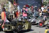 Pengunjung mengamati motor vespa modifikasi saat pemecahan rekor muri parkir vespa tank dan army look terbanyak di Gor Jayabaya Kota Kediri, Jawa Timur, Minggu (4/8/2019). Kegiatan bertajuk Kediri Scooter Festival berhasil memecahkan rekor muri parkir motor vespa tank dan army look sejumlah 250 unit yang dipersembahkan sebagai kado Hut ke-1140 Kota Kediri. Antara Jatim/Prasetia Fauzani/zk