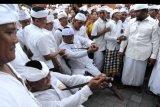 Umat Hindu yang kesurupan menusukkan keris ke tubuhnya saat Tradisi Ngerebong di Pura Dalem Pengrebongan, Denpasar, Bali, Minggu (11/8/2019). Tradisi tersebut dilakukan bertujuan menyucikan alam dan menetralisir kekuatan negatif sekaligus untuk menciptakan keharmonisan. ANTARA FOTO/Fikri Yusuf/nym.