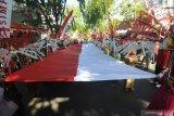 Peserta membawa bendera merah putih berukuran besar saat Karnaval Budaya di Pamekasan, Jawa Timur, senin (12/8/2019). Karnaval yang diikuti sekolah dari tingkat SD sampai SMA yang bertema