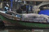TERDAMPAK TUMPAHAN MINYAK, TANGKAPAN NELAYAN BANTEN MENURUN. Nelayan memperbaiki jaring di Pelabuhan Perikanan Nusantara (PPN) Karangantu, Serang, Banten, Senin (12/8/2019). Kepala PPN Karangantu Asep Saefulloh mengungkapkan, hasil tangkapan para nelayan di Teluk Banten terus menurun terdampak sisa-sisa tumpahan minyak yang terbawa arus dari Perairan Karawang hingga mengotori alat tangkap nelayan setempat serta hasil melaut terus menyusut sebab tumpahan minyak mematikan sebagian ikan terutama yang masih kecil. ANTARA FOTO/Asep Fathulrahman/