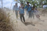 Sejumlah siswa pulang sekolah melewati jalan berdebu dari SD 'kelas jauh' (Filial) Dusun Cobbuk yang menginduk di SDN 8 Curah Tatal, Arjasa, Situbondo, Jawa Timur, Selasa (13/8/2019). Puluhan siswa SD Filial tersebut berangkat dan pulang sekolah melewati jalan rusak, berdebu sekitar 3 kilometer perjalanan. Antara Jatim/Seno/zk
