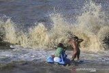 Sejumlah anak bermain di antara ombak di pantai Juntinyuat, Indramayu, Jawa Barat, Selasa (13/8/2019). BMKG menyatakan gelombang di perairan laut Jawa mencapai 3 meter akibat angin kencang. ANTARA FOTO/Dedhez Anggara/agr
