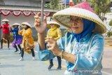 Sejumlah warga binaan menari tarian kolosal saat mengikuti pemecahan rekor Museum Rekor Dunia Indonesia (MURI) Tari Kolosal Indonesia Bekerja di Lembaga Pemasyarakatan (Lapas) Kelas II A, Karawang, Jawa Barat, Kamis (15/8/2019). Pemecahan rekor tersebut dilakukan oleh 200 ribu warga binaan dan petugas lapas yang digelar serentak di seluruh Indonesia untuk memperingati HUT ke-74 Republik Indonesia. ANTARA FOTO/M Ibnu Chazar/agr