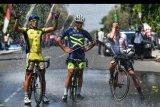 Sejumlah pebalap sepeda membahasi dirinya dengan air seusai finish etape pertama Tour de Indonesia 2019 di alun-alun Kabupaten Ngawi, Jawa Timur, Senin (19/8/2019). Etape pertama dimulai dari Candi Borobudur, Jawa Tengah dan berakhir di alun-alun Kabupaten Ngawi Jawa Timur dengan jarak tempuh 186,6 Km. ANTARA FOTO/Sigid Kurniawan/nym.