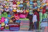 Seorang penjual boneka menata boneka di Kampung Boneka, Cikampek Utara, Karawang, Jawa Barat, Rabu (21/8/2019). Kampung boneka atau sentra produksi boneka memiliki sekitar 300 perajin boneka yang dapat memproduksi 3000 hingga 5000 boneka per bulan dengan harga jual Rp2.500 - Rp450.000 per boneka tergantung ukuran. Kampung boneka tersebut juga masuk dalam salah satu nominasi kategori destinasi belanja terpopuler Anugerah Pesona Indonesia 2019. ANTARA JABAR/M Ibnu Chazar/agr