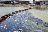 Warga melintas disekitar tambak ikan yang terdampak tumpahan minyak mentah di Desa Cemarajaya, Cibuaya, Karawang, Jawa Barat, Jumat (30/8/2019). Akibat pasangnya air laut, tumpahan minyak mentah di laut utara Karawang terbawa arus sampai ke tambak ikan milik warga yang dekat dengan bibir pantai. ANTARA FOTO/M Ibnu Chazar/agr