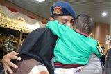 Seorang personil Brimob Polda Kalbar memeluk anak dan istrinya sesaat sebelum keberangkatan pasukan Bantuan Kendali Operasi (BKO) Brimob di Bandara Supadio, Kabupaten Kubu Raya, Kalimantan Barat, Kamis (29/8/2019) malam. Polda Kalbar mengirim 250 personil Brimob ke Papua untuk melaksanakan tugas pengamanan pasca konflik di daerah tersebut. ANTARA FOTO/Jessica Helena WuysangANTARA FOTO/JESSICA HELENA WUYSANG (ANTARA FOTO/JESSICA HELENA WUYSANG)