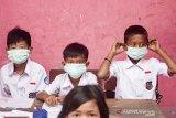 Sejumlah siswa memakai masker yang diberikan oleh petugas medis di SDN 1 Cemarajaya, Karawang, Jawa Barat, Selasa (3/9/2019). Pertamina bersinergi bersama Pertamedika memberikan pelayanan kesehatan gratis dan membagikan masker serta mengedukasi siswa berupa penyuluhan tentang menjaga kebersihan dan kesehatan di wilayah terdampak tumpahan minyak mentah. ANTARA FOTO/M Ibnu Chazar/agr