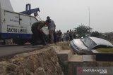 Hindari tabrakan, minibus ini terguling dari jalan hingga menimpa kuburan