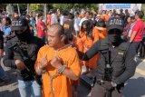 Polisi menggiring tersangka bandar dan kurir narkoba di tengah kerumunan warga saat konferensi pers di sela kegiatan hari bebas kendaraan di Lapangan Puputan Margarana Renon, Denpasar, Bali, Minggu (8/9/2019). Polresta Denpasar menghadirkan 17 tersangka terkait kasus narkotika dalam tiga bulan terakhir di ruang publik termasuk memperlihatkan barang bukti narkotika berupa 3,2 Kg sabu-sabu, 16 butir ekstasi, 74,29 gram ganja, 1,9 gram kokain dan 1.316 butir pil koplo untuk mengedukasi masyarakat bahaya narkoba. ANTARA FOTO/Nyoman Hendra Wibowo/nym.