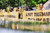 Seorang pengunjuk rasa yang tergabung dalam Koalisi Masyarakat Sipil Karawang membentangkan poster saat melakukan aksi solidaritas untuk pesisir Karawang di depan kantor DPRD, Karawang, Jawa Barat, Sabtu (14/9/2019). Aksi tersebut bertujuan untuk menuntut pemerintah Kabupaten Karawang melakukan pendampingan kepada masyarakat pesisir dan memulihan ekosistem laut, pantai dan mangrove serta melakukan audit terhadap seluruh pihak terkait terdampak tumpahan minyak di pesisir Karawang. ANTARA JABAR/M Ibnu Chazar/agr